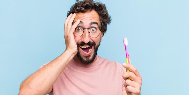 Jeune homme barbu levant les mains à la tête, bouche bée, se sentant extrêmement chanceux, surpris, excité et heureux