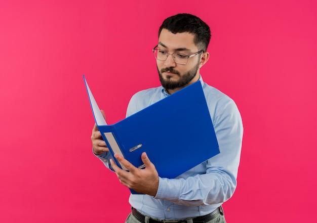 Jeune homme barbu à lunettes et chemise bleue regardant dossier avec visage sérieux
