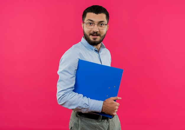 Jeune homme barbu à lunettes et chemise bleue tenant le dossier avec le sourire sur le visage