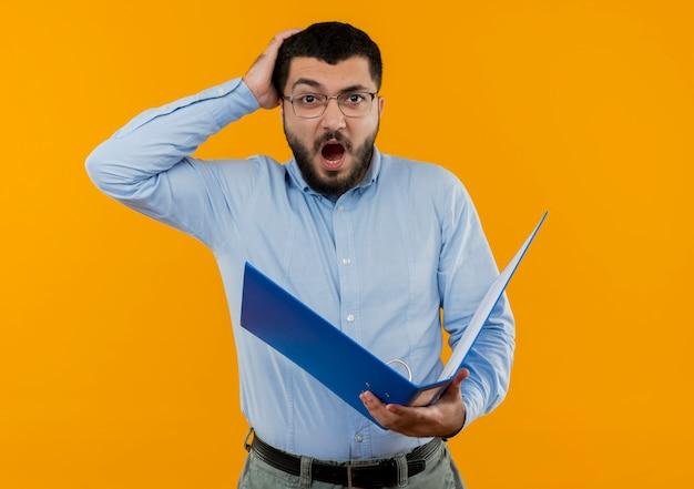 Jeune homme barbu à lunettes et chemise bleue tenant grand dossier surpris et étonné