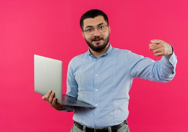 Jeune homme barbu à lunettes et chemise bleue tenant un ordinateur portable pointant avec le doigt à la caméra souriant confiant