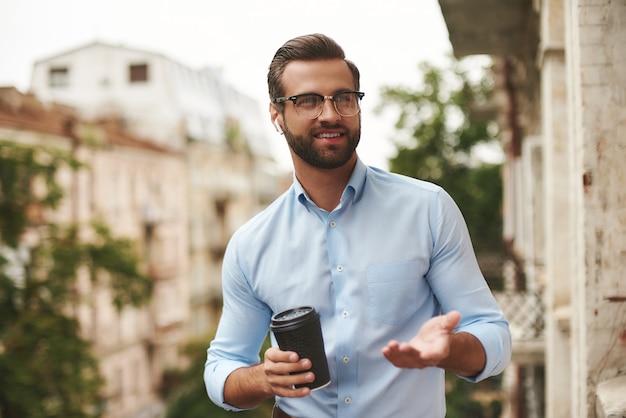 Jeune homme barbu à lunettes et écouteurs tenant une tasse de café et parlant avec un ami