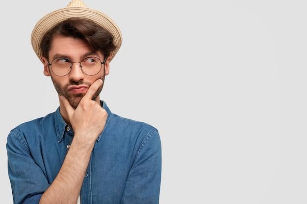 Jeune homme barbu avec des lunettes rondes et une chemise en jean