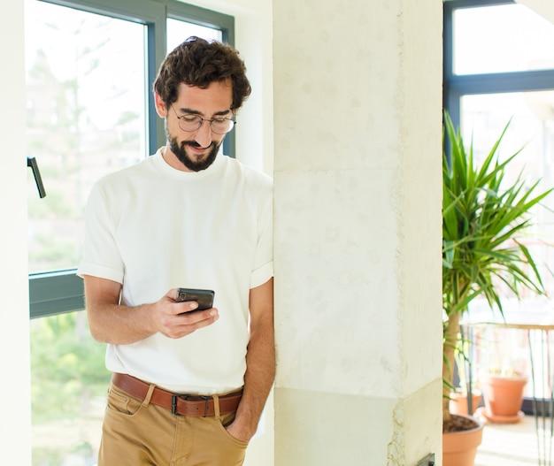 Jeune homme barbu à la maison. en utilisant un téléphone intelligent
