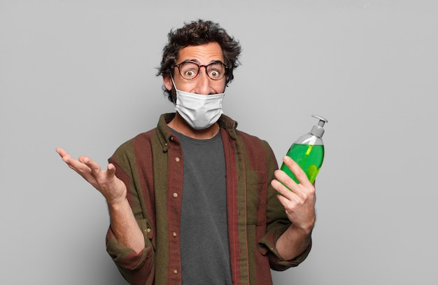 Jeune homme barbu avec un masque médical et une bouteille de savon