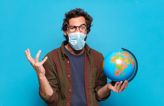 Jeune homme barbu avec un masque médical et un modèle de carte du monde