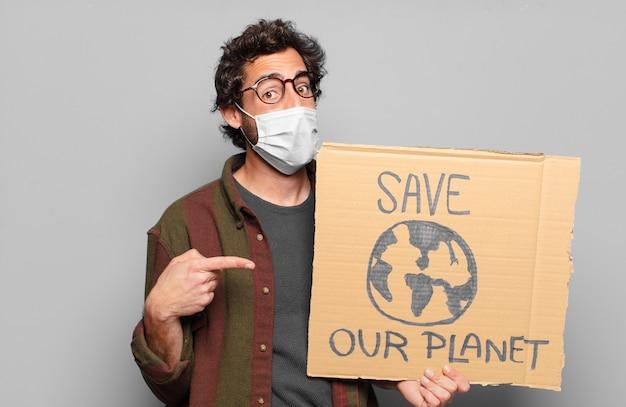 Jeune homme barbu avec un masque médical et sauver notre planète board