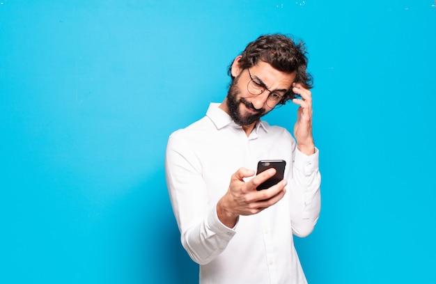 Jeune homme barbu montrant son écran de cellule