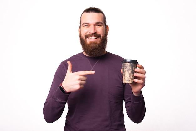 Jeune homme barbu montre une tasse de boisson chaude qu'il tient et regarde la caméra sourit