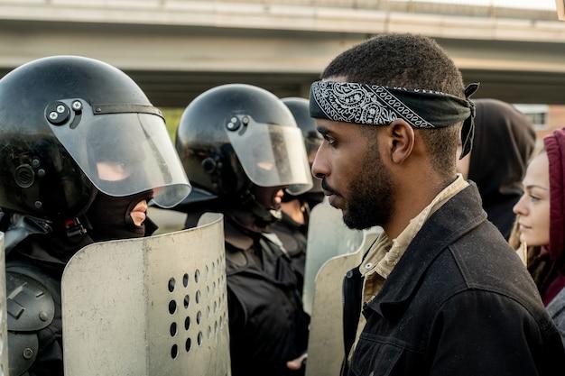 Jeune homme barbu noir mécontent en bandana debout devant des policiers avec des casques anti-émeute et des boucliers à l'extérieur