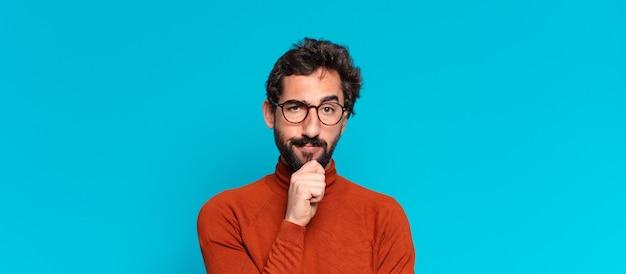 Jeune homme barbu. penser ou douter de l'expression. concept d'espace de copie