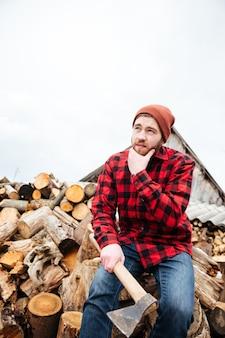 Jeune homme barbu pensif en chemise à carreaux et chapeau avec bûche assis sur des bûches et pensant