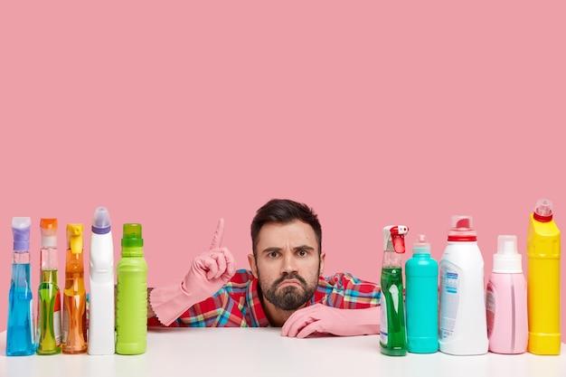 Un jeune homme barbu perplexe pointe vers le haut, a une expression mécontente, montre de la place pour nettoyer, utilise des détergents de haute qualité