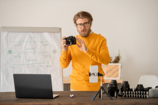 Jeune homme barbu avec photocamera expliquant comment prendre des photos à son public en ligne devant l'appareil photo du smartphone