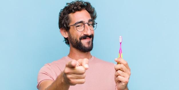 Jeune homme barbu pointant avec un sourire satisfait, confiant et amical, vous choisissant