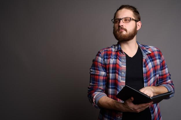 Jeune homme barbu portant une chemise à carreaux contre un mur gris