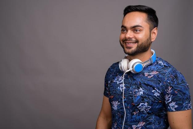 Jeune homme barbu portant des écouteurs contre le gris