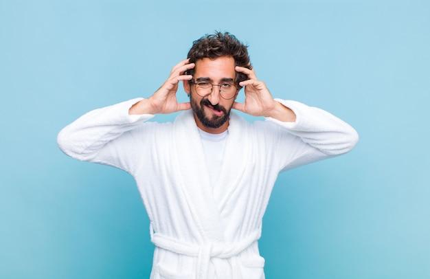 Jeune homme barbu portant un peignoir de bain frustré et ennuyé, malade et fatigué de l'échec, marre des tâches ennuyeuses et ennuyeuses