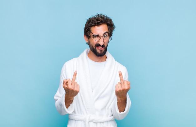 Jeune homme barbu portant un peignoir de bain provocant, agressif et obscène, retournant le majeur, avec une attitude rebelle