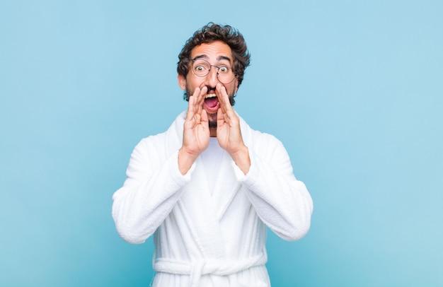 Jeune homme barbu portant un peignoir de bain se sentir heureux, excité et positif, donnant un grand cri avec les mains à côté de la bouche, appelant