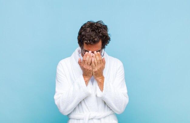 Jeune homme barbu portant un peignoir de bain triste