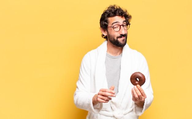 Jeune homme barbu portant un peignoir avec un beignet au chocolat
