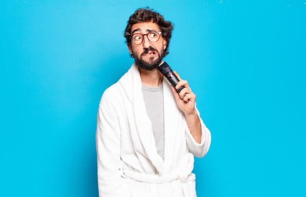 Jeune homme barbu portant un peignoir. concept de soins de cheveux ou de barbe
