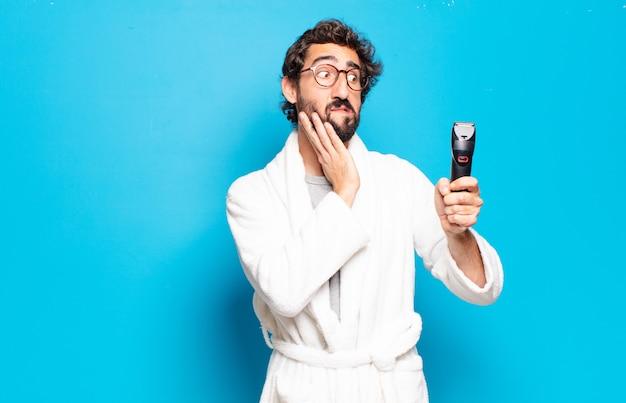 Jeune homme barbu portant un peignoir. concept de soins des cheveux ou de la barbe