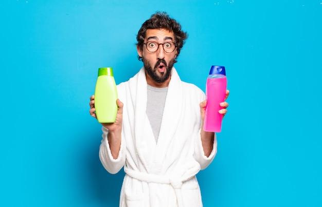Jeune homme barbu portant un peignoir avec du shampoing et des produits de beauté
