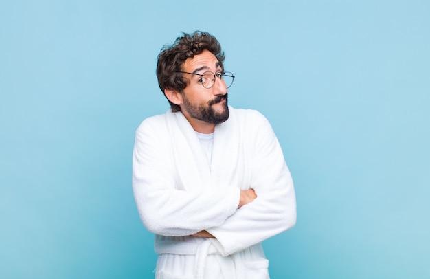 Jeune homme barbu portant un peignoir en haussant les épaules, se sentant confus et incertain, doutant des bras croisés et regard perplexe