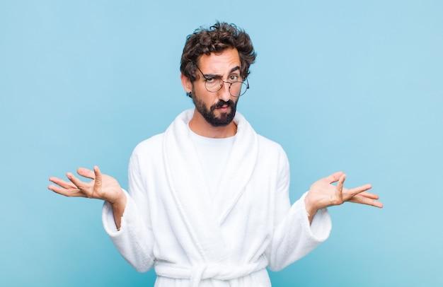 Jeune homme barbu portant un peignoir à la perplexité