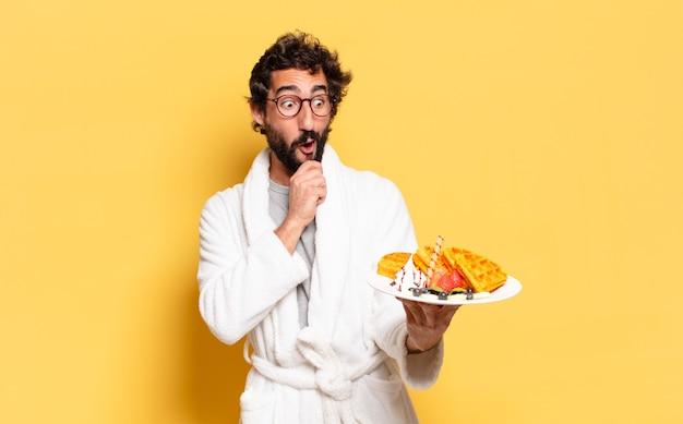 Jeune homme barbu portant un peignoir et prenant son petit déjeuner