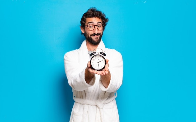 Jeune homme barbu portant un peignoir et un réveil