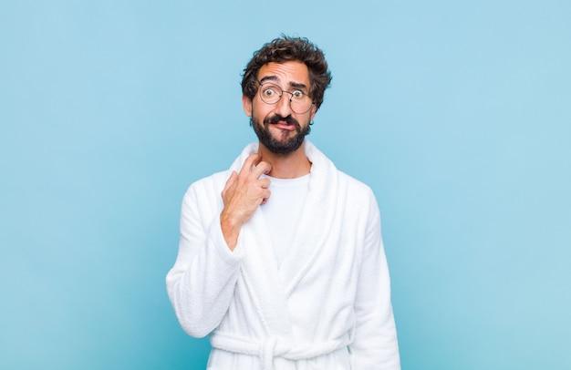 Jeune homme barbu portant un peignoir se sentant stressé, frustré et fatigué, frottant le cou douloureux, avec un regard inquiet et troublé