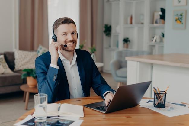 Jeune homme barbu positif indépendant portant un costume dans des écouteurs avec microphone souriant à la caméra alors qu'il était assis sur son lieu de travail à la maison, utilisant un ordinateur portable pour le travail et ayant une réunion en ligne