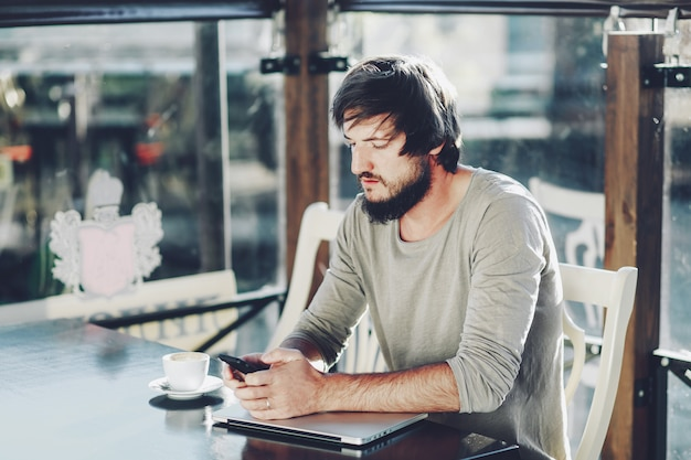 Jeune homme barbu regardant intensément sur l'écran du téléphone portable