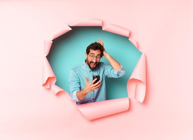 Jeune homme barbu regardant le téléphone