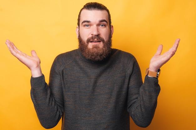 Un jeune homme barbu regarde et montre que je ne sais pas chanter est confus