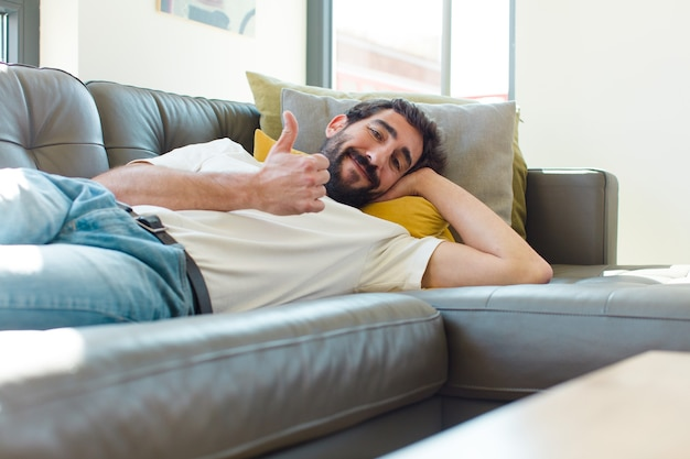 Jeune homme barbu reposant sur un canapé