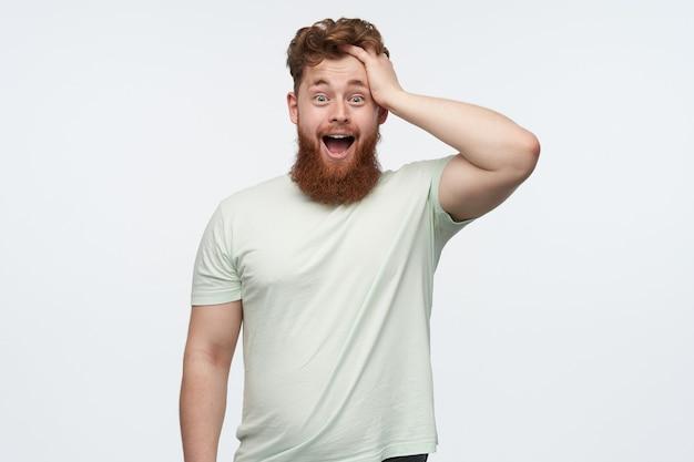 Jeune homme barbu rousse étonné, garde la bouche et les yeux largement ouverts, tient sa tête avec la main.