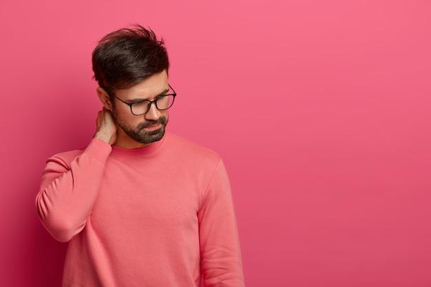 Jeune homme barbu se concentre, a des douleurs au cou, des massages et des touches avec la main