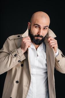 Un jeune homme barbu se lève et ajuste son imperméable sur un fond noir.