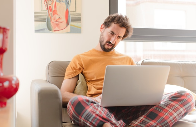 Jeune homme barbu se sentant perplexe et confus avec une expression stupéfaite en regardant quelque chose d'inattendu et assis avec un ordinateur portable