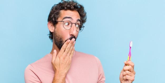 Jeune homme barbu se sentir heureux, choqué et surpris, couvrant la bouche avec la main et pointant vers l'espace de copie latérale