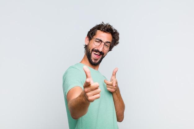 Jeune homme barbu se sentir heureux, cool, satisfait, détendu et réussi, pointant la caméra, vous choisissant