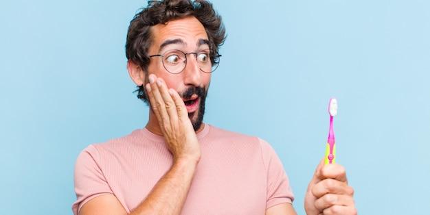 Jeune homme barbu se sentir heureux, excité et surpris, regardant sur le côté avec les deux mains sur le visage