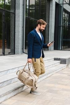 Jeune homme barbu séduisant portant une veste marchant à l'extérieur dans la rue, sac de transport, tenant un téléphone portable