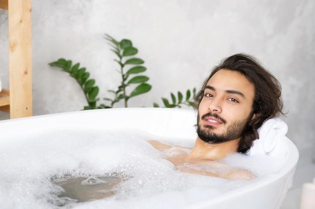 Jeune homme barbu serein se détendre en position couchée dans le bain avec de l'eau chaude et de la mousse devant la caméra