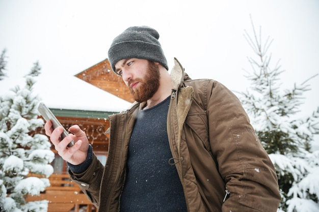 Jeune homme barbu sérieux à l'aide de smartphone debout à l'extérieur en hiver