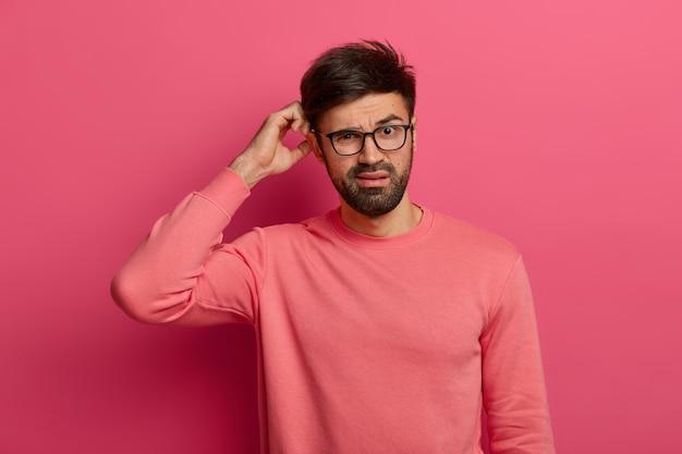 Un jeune homme barbu sérieux se gratte la tête, réfléchit profondément à la façon de résoudre le problème